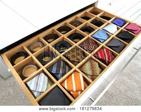 many colored ties and belts in the wide drawer