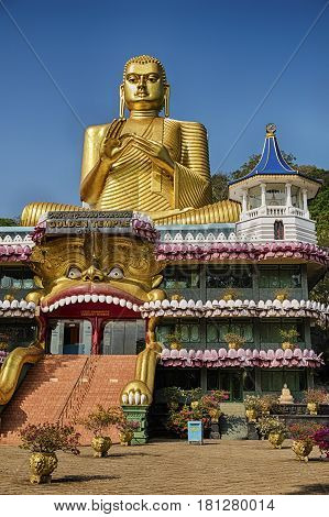 The entrance to the main hall of the Golden Temple of Dambulla lies under the giiant gold statue of Buddha.
