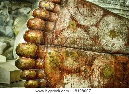 Detail view of Buddha's feet that are painted in bright colors and patterns in the Golden Temple cave temple complex at Dambulla in Sri Lanka.
