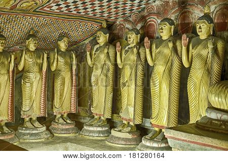 A row of Buddha statues line the inside of a cavern in the Dambulla cave comples near Kandalarma in Sri Lanka.