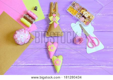 Stuffed Easter bunny toy with hearts sewn from felt. Scissors, pins, thread, thimble, buttons and beads in box, paper template, felt sheets on lilac wooden table. Children Easter crafts. Top view