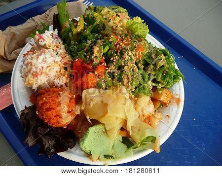 Hawaiian poki bowl with avocado ,lettuce,crab and roe on blue tray