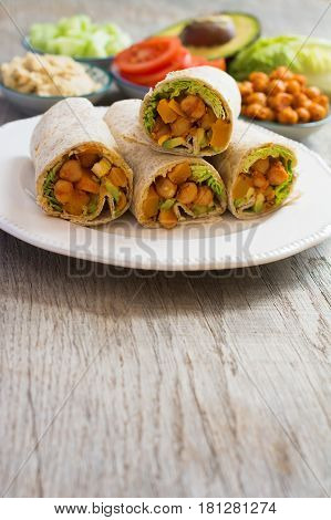 Vegetarian tortillas with chickpeas butternut squash spring onion cucumber avocado with ingredients on the back on the dark wooden table copy space for text