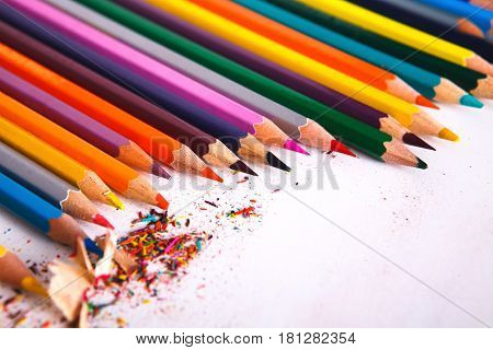 Drawing, art and education background. Lot of colorful pencils frame with sawdust and shavings on white, copy space, flat lay