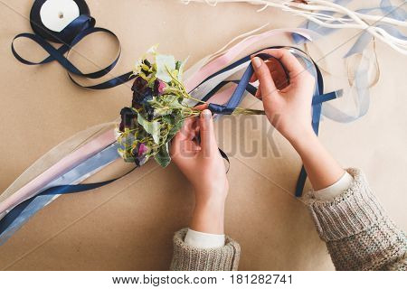 Handmade art, fancywork master class. Unrecognizable woman wrap artificial flowers bouquet with blue ribbon, flat lay.