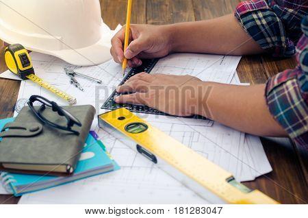 Engineering draftsman is working in the office.