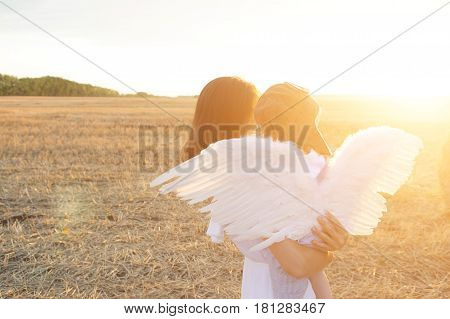 Mother And Son Having Fun. Boy In A Pilot Hat And Angel Wings Sitting On Hands Of His Mother And Loo