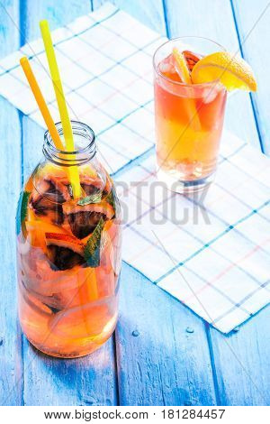 Detox water with various citrus fruit. Bottle and drinking glass with slices of orange, blood orange, lemon and grapefruit. Blue plank background