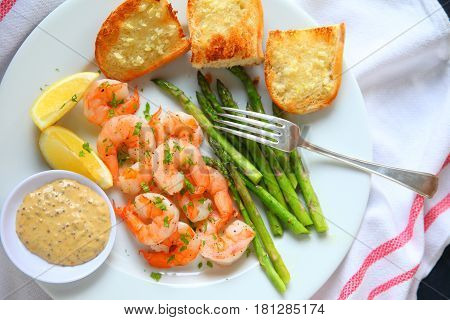 Overhead view of shrimp with asparagus and garlic bread with lemon and a tangy dipping sauce