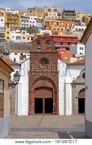 SAN SEBASTIAN DE LA GOMERA, LA GOMERA, SPAIN: Church of the Assumption in San Sebastian de la Gomera with colorful houses in the background