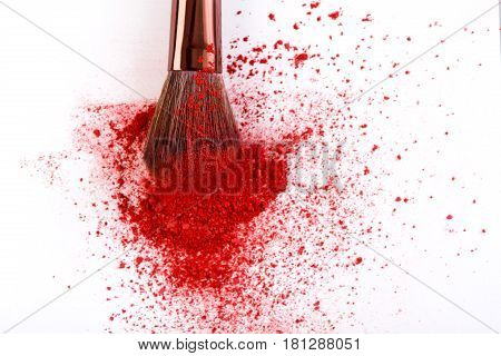 Makeup brush background with red blush sprinkled on white. Make up and female cosmetics background