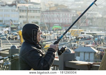 ISTANBUL, TURKEY - 1 APRIL , 2017: Fishermen on the Galata Bridge fish in the Golden Horn Bay Turkey