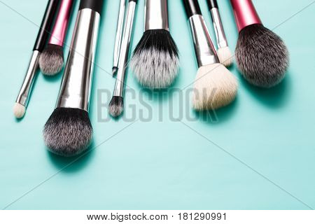 Makeup brushes, everyday make-up tools. Cosmetic essentials on bright blue background, closeup