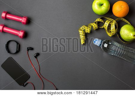 Athlete's set with bottle of water on dark gray background. Top view. Still life. Copy space
