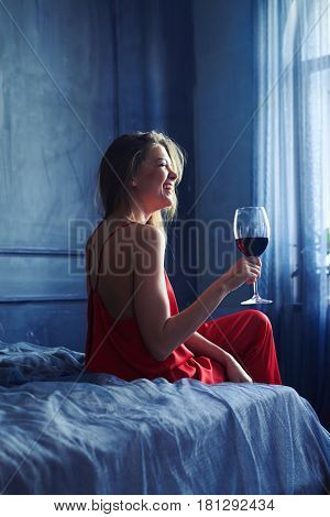 Back view of a beautifuly laughing woman with glass red wine on the bed. Woman drinking wine. Obscure atmosphere in the room, female sitting on the bed isolated in bedroom