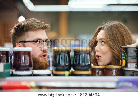 Inspired glad man and woman hiding near shelf with jam in mall