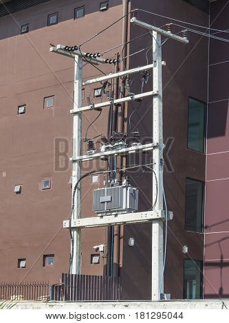 Electricity Distribution Transformer on poles in fornt of brown building