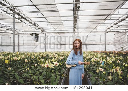 Young pretty woman with red hairs and guitar in hands looking at white flowers in orangery