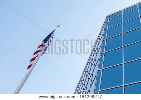 Blue Glass Building Parallel to a Flag Against the Sky