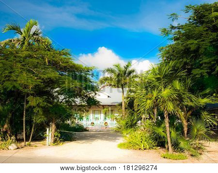 Tropical front garden with driveway leading to the gate of a wooden house in Cayman Islands