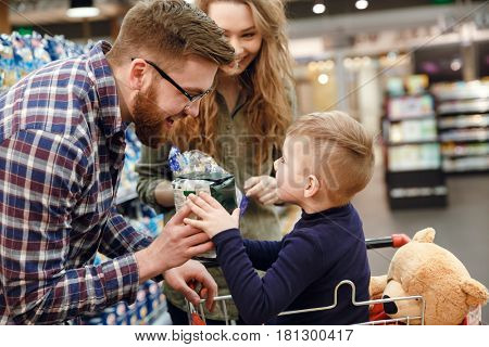 Side view of Bearded man giving convenience food to the boy while woman standing near them