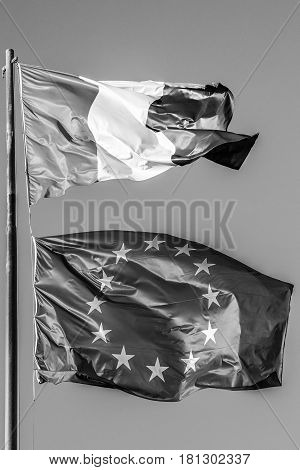 general three colors flag and Europe flag waving together in isolated the grey sky background. black and white. Concept for old financial treated, unique currency and financial bond and crisis.