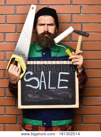 bearded man long beard brutal caucasian hipster with moustache holding various building tools: saw hammer roller paint and board with inscription sale with serious face on brick wall background
