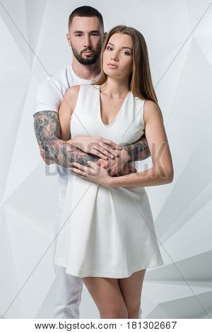 Young casual couple with woman holding his hands over woman's shoulder and looking for the camera. Man and woman in white clothes on a white background