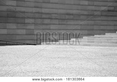A black and white image of a wall and steps creating a background.