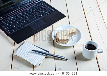 Business still life a notebook is opened mug with coffee notebook with a pen and sweetnesses on a wooden table.