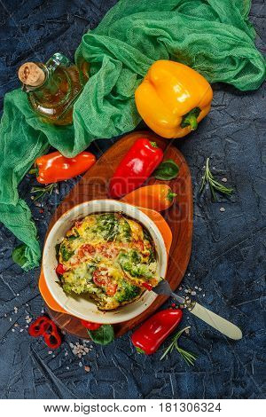 Frittata with broccoli spinach sweet peppers and tomatoes in ceramic baking dish. Italian omelet with vegetables. Top view