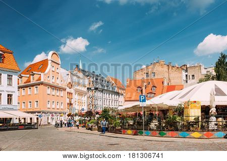 Riga, Latvia - July 2, 2016: People Walking Near Open Air Leisure Venue Recreation Center Egle In Sunny Day In Old Town On Kalku Street.
