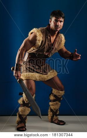 The handsome caveman is holding a sword.