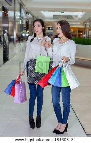 Two Cute Girl Walks In A Mall With Gift Bags.