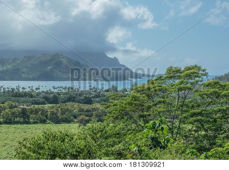 Lush Land and Blue Sea: Hanalei bay on a cloudy day, with mountains and lush green landscape, on Kauai