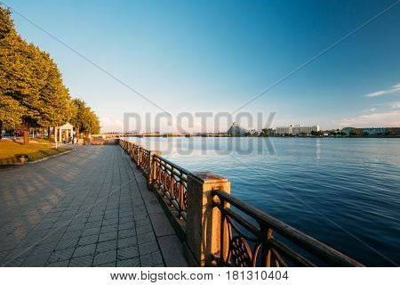 Riga, Latvia - July 1, 2016: City promenade near Daugava River, National Library Building And Hotel Radisson Blu At Scenic Embankment Pier Under Blue Sky At  Sunset Evening Time.