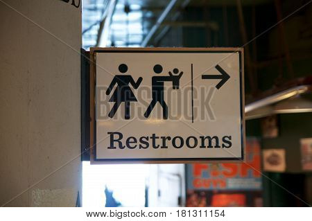 SEATTLE, WASHINGTON, USA - JAN 24th, 2017: a lady and a man toilet sign on white background, way or direction to the restroom at the Pike Place Market.