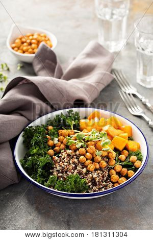 Green and healthy vegan grain bowl with quinoa, butternut squash, kale and roasted chickpeas