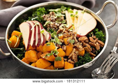 Healthy vegan grain bowl with quinoa, butternut squash, kale and apple