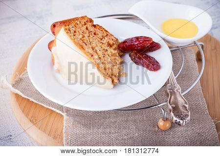 Slice of date cake and dates on a white plate