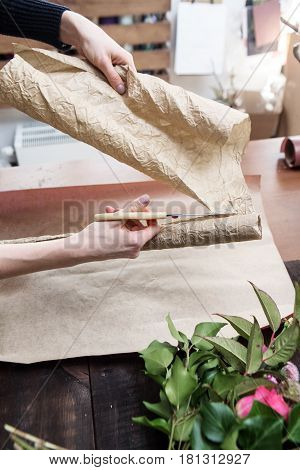 florist's hands cutting paper for covering flowers