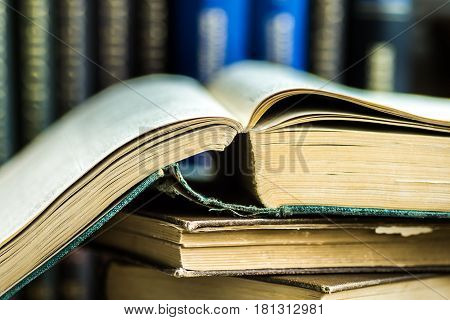 Stack of opened old books on wood table volumes in the background reading education concept selective focus close up