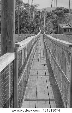 Walk Across: looking across the historic suspension bridge in Old Hanapepe Town, in black and white, on Kauai, Hawaii, mid morning, on March 28, 2017