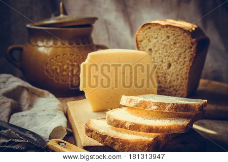Loaf of sourdough sliced bread on wood cutting board chunk of cheese clay dishware knife rural kitchen interior slightly toned