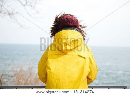 Back view shot of woman looking away at sea in yellow raincoat
