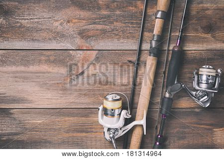 Fishing rods and reels with line on wooden background with free space. Toned image.