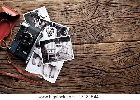 Old rangefinder camera and black-and-white photos on the old wooden table.