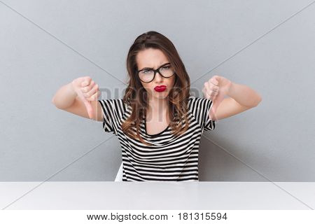 Photo of sad young lady wearing glasses sitting over grey wall. Looking at camera showing thumbs down.