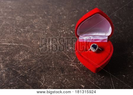 Red box with a silver ring with a black stone on a dark marble background. Object on a dark background. Transparent object. Conceptual object. The objects are on the table. The object is on marble. The object lies on the surface