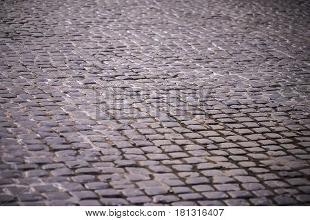 Cobblestone pavement, stone street pavement background with selective focus. Stone road texture, cobblestone backgrounds